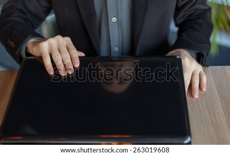 Man Opening His Laptop on The Table