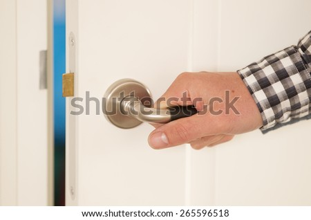 Man opens door of a house or a room - stock photo