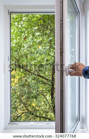 man opens pvc window, which you can see green of a tree park in the ecologically clean area of the city with fresh air - stock photo
