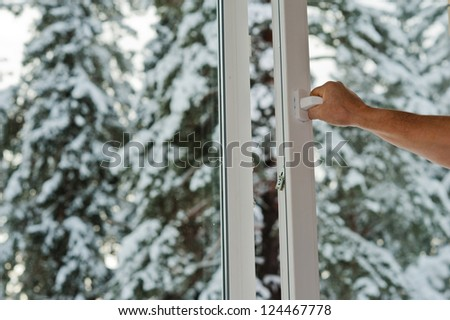 man opens the plastic window with forest view - stock photo