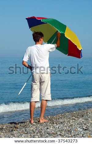 Man opens umbrella on seaside