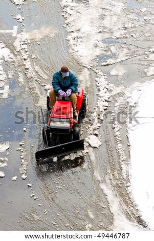 Man operating machine removing snow from street - stock photo