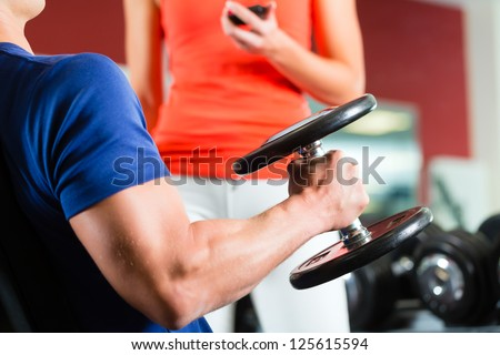 Man or Bodybuilder with his personal fitness trainer in the gym exercising with dumbbells, closeup