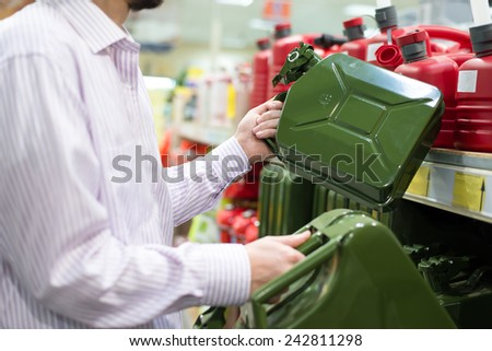man or woman holding two sizes of green cans and shopping shelve on the background - stock photo