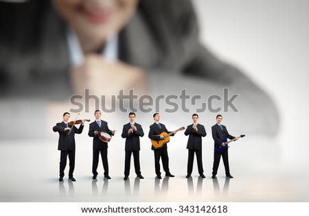Man orchestra playing different music instruments and woman leader