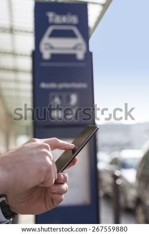 Man orders a taxi from his mobile phone. Close-up hands - stock photo