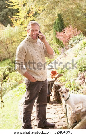 Man Outdoors On Mobile Phone With Dog Whilst On Break From Gardening - stock photo