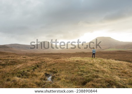 Man overlooking view of Scottish mountains during sunset in Autumn on the Isle of Skye, Scotland - stock photo