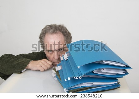 Man overwhelmed with file/Overworked Office Worker/Mature office worker overwhelmed with files - stock photo