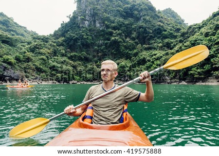 Man paddle on kayak in Halong Bay laguna. Front view on kayaker and island on the background. Adventure on water.