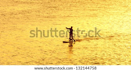man paddleboarding at sunset with dog - stock photo