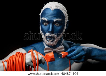 Man painted in blue color with snowy hair and beard holds the power cord with plug  on black background