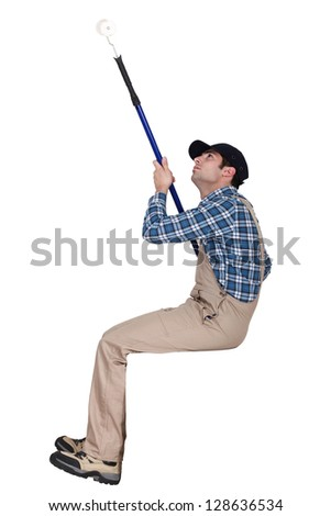 Man painting a ceiling with a roller - stock photo