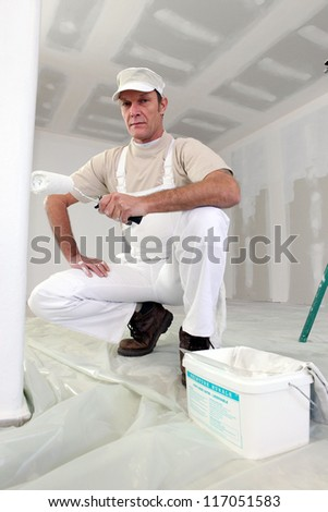 Man painting a room white
