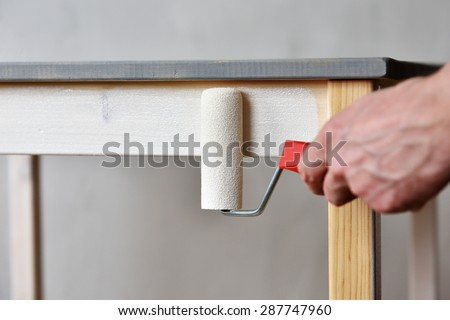 Man painting a wooden table using paint roller  - stock photo