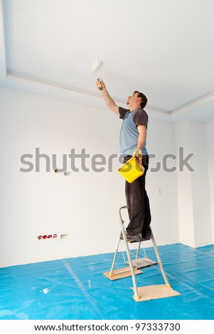 Man painting ceiling of new apartment - stock photo