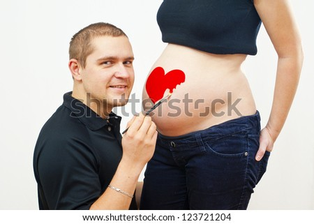 man painting on pregnant woman - stock photo