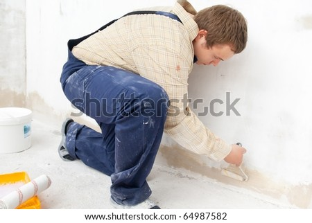 Man painting wall with small roller - stock photo