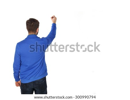 Man paints on a white wall. Man drawing on the wall. Advertising concept. Man writing on white wall background. Man that write on a blank space. Copy space for text. Man back to camera. - stock photo