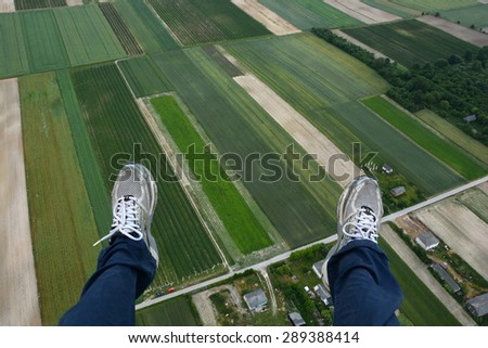 Man paragliding above  fields of crops  - stock photo