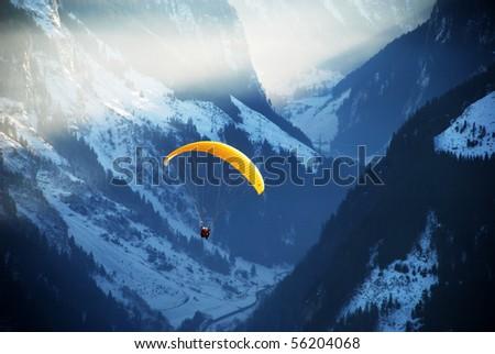 Man paragliding over mountains - stock photo