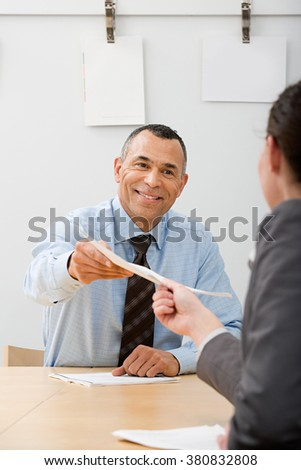 Man passing file to colleague - stock photo