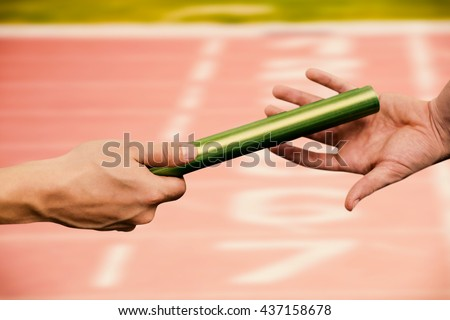 Man passing the baton to partner on track against close up of the track starting point - stock photo
