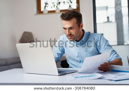 Man paying bills at home on his laptop.