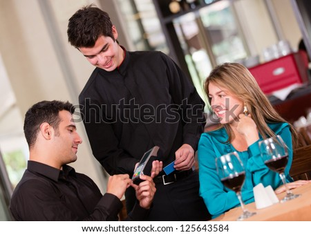Man paying by credit card at a restaurant - stock photo