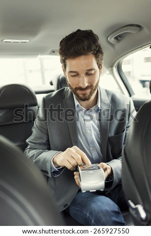 Man paying the taxi with the credit card. Typing code