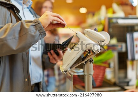 Man paying with credit card at supermarket checkout - stock photo