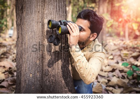 Man peeking from behind a tree in forest with binoculars.  - stock photo