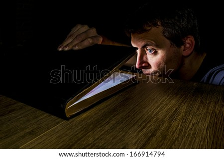 man peeking in a book filled with light - stock photo