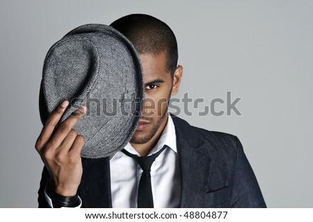 Man peeks from behind his fedora in studio - stock photo