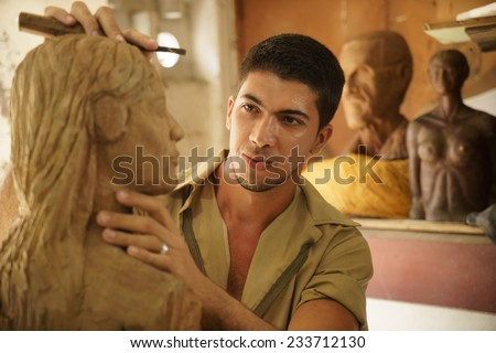 Man, people, job, young student at work learning craftsman profession in art class, working with wooden statue and carving wood - stock photo