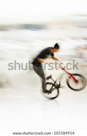 man performing stunts on bike in brightly lit space in singapore - stock photo