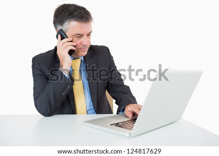 Man phoning while writing on laptop on a white background