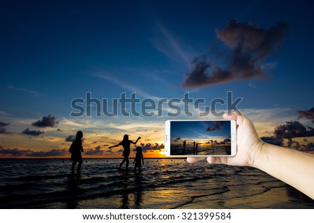 Man photographed sunset and his family on the beach with his Smart phone, Beautiful , sharp images and realistic , Phuket Thailand. - stock photo