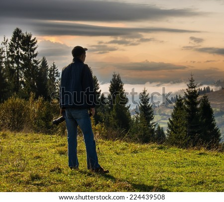 Man photographer in the mountains in autumn at sunset - stock photo