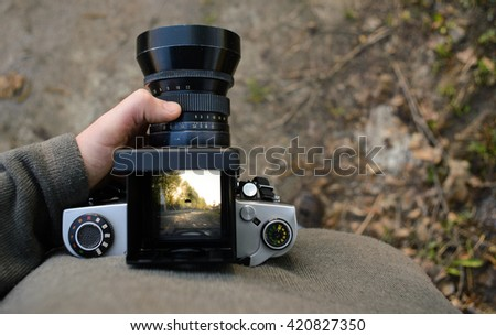 man photographer is making landscape photography with old film camera in spring or summer, tourism and hiking concept. top view. copy space - stock photo