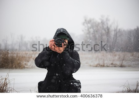Man photographer looking at camera and taking picture on digital camera (DSLR) Is snowing and man is enjoying the beautiful winter view.  - stock photo