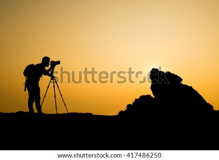 man photographer taking photo on sunset mountain