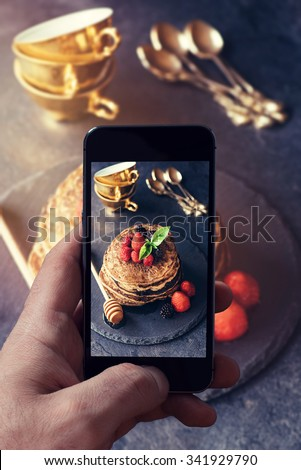 Man photographing buckwheat pancakes with berry fruit and honey on dark background  - stock photo