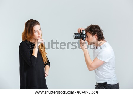 Man photographing female model isolated on a white background - stock photo