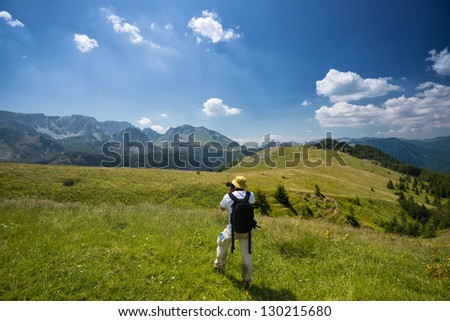 Man photographing in nature. He is taking a picture with camera in a nature. - stock photo