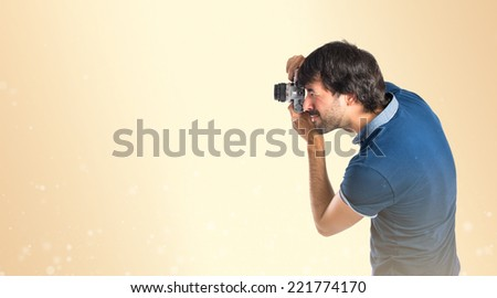 Man photographing over ocher background