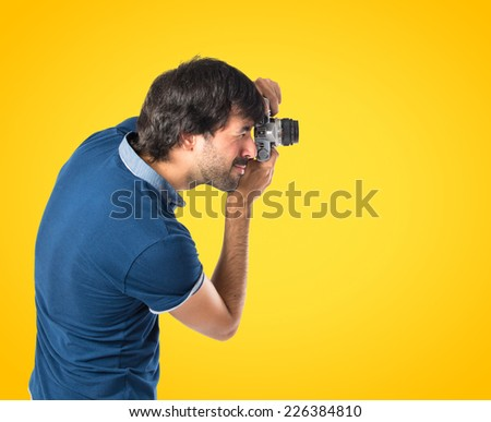 Man photographing over yellow background