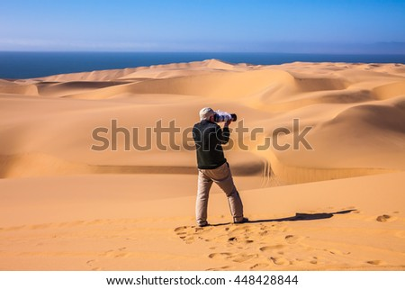 Man photographing sand dunes. The west coast of the Atlantic Ocean. Sandwich Harbour - part of Namib-Naukluft National Park, Namibia