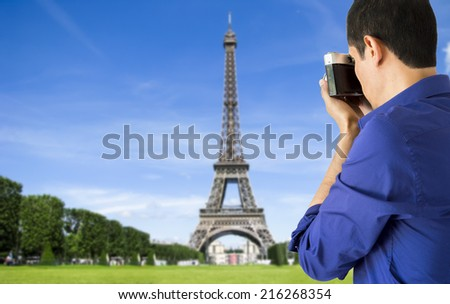 man photographing with camera old tower eiffel in paris