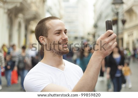 Man photographing with mobile phone walking, background is blured city - stock photo